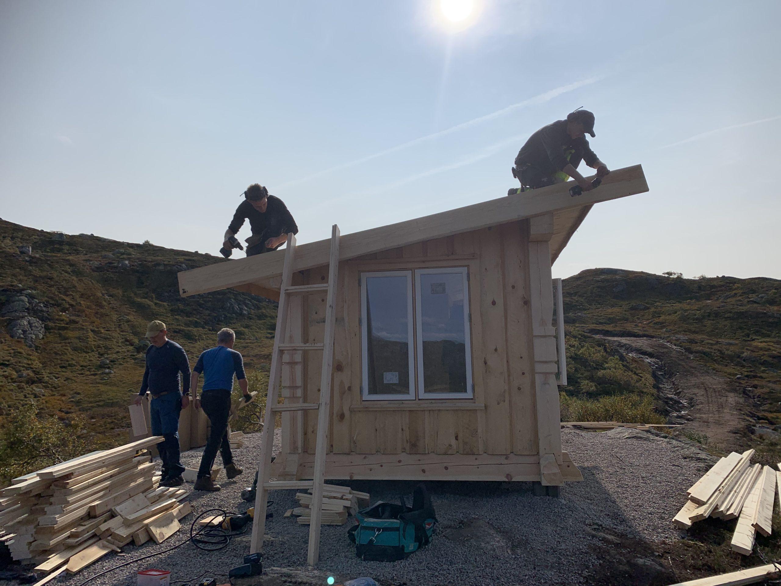 På taket jobber Kenneth og Jon Kristian. Velformann Erik er i full sving med å gjøre om kapp om til rett lengde ved.